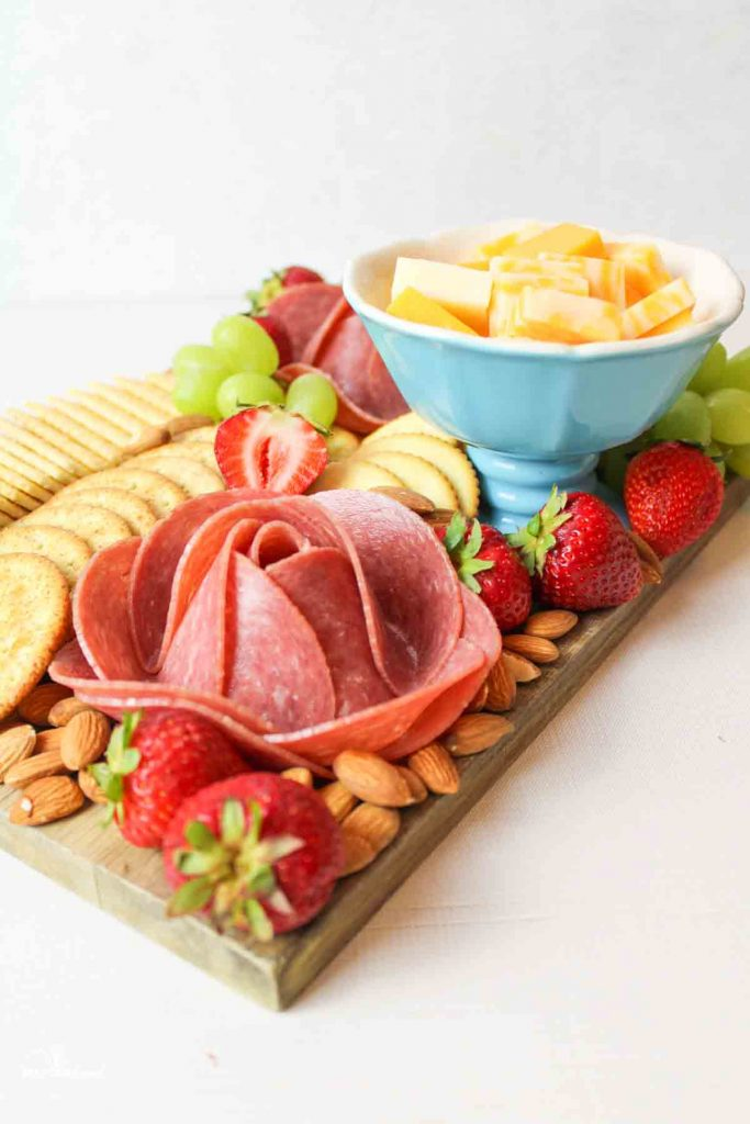 an angled wooden charcuterie board featuring meat flowers, crackers, cheese, nuts and fruit