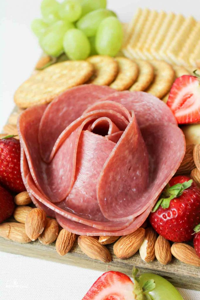 a close up view of a meat rose on a charcuterie board