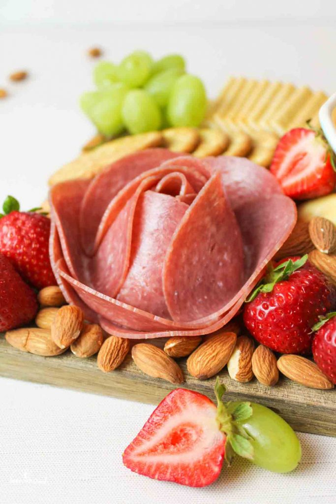 a meat flower on a charcuterie board with strawberries and almonds around it