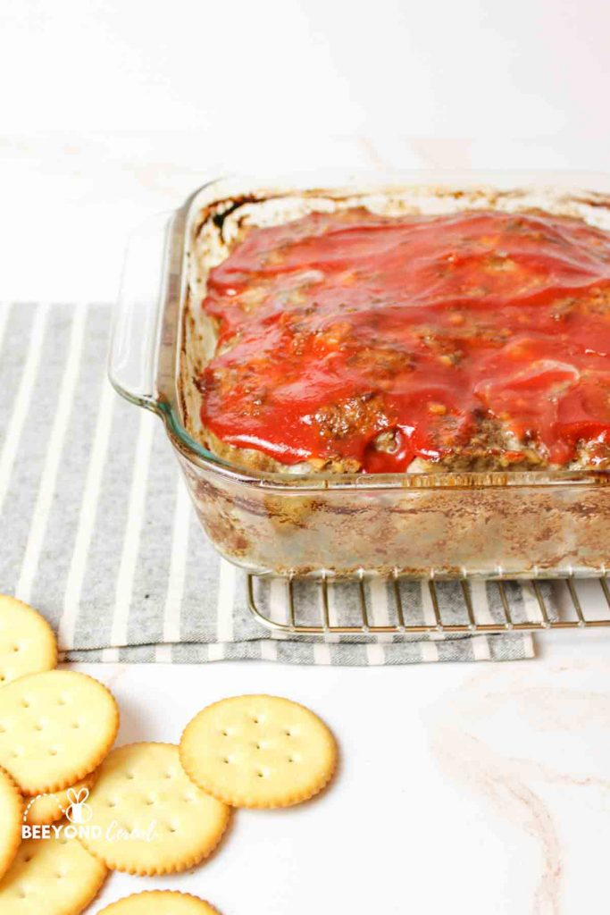 an angled view of a glass baking dish filled with meatloaf and topped with kethcup and a pile of crackers to the bottom corner