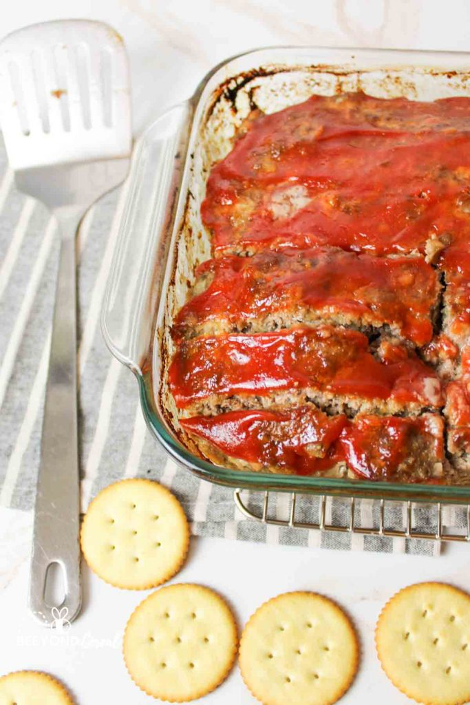 sliced meatloaf in a baking dish with a spatula to the left and ritz crackers down below