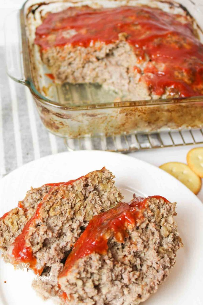 sliced meatloaf on a plate with more in a pan in background