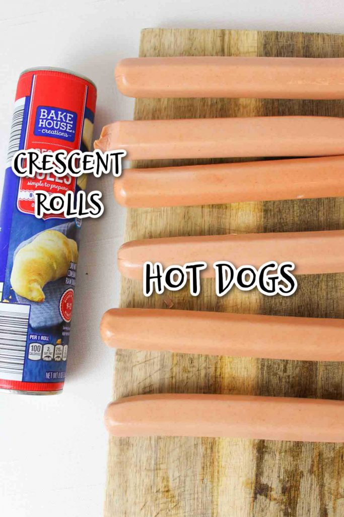 crescent rolls in a can and a board with hot dogs laying on it