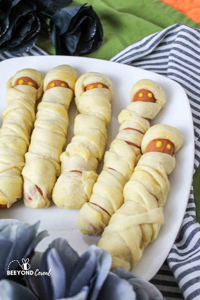a plate with 5 hot dog mummys with mustard eyes