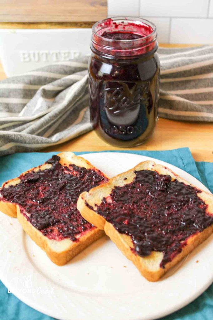 two slices of toast topped with sugar free blueberry jam and a jar full of jam in the background