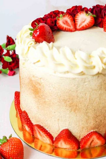 a close up of a layered tres leches cake with strawberries and red flowers