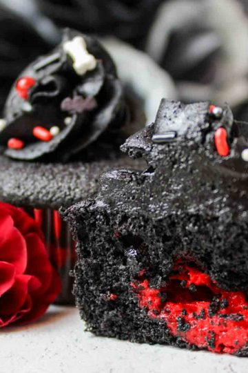 a close up of black velvet vampire cupcakes with red filling next to a flower
