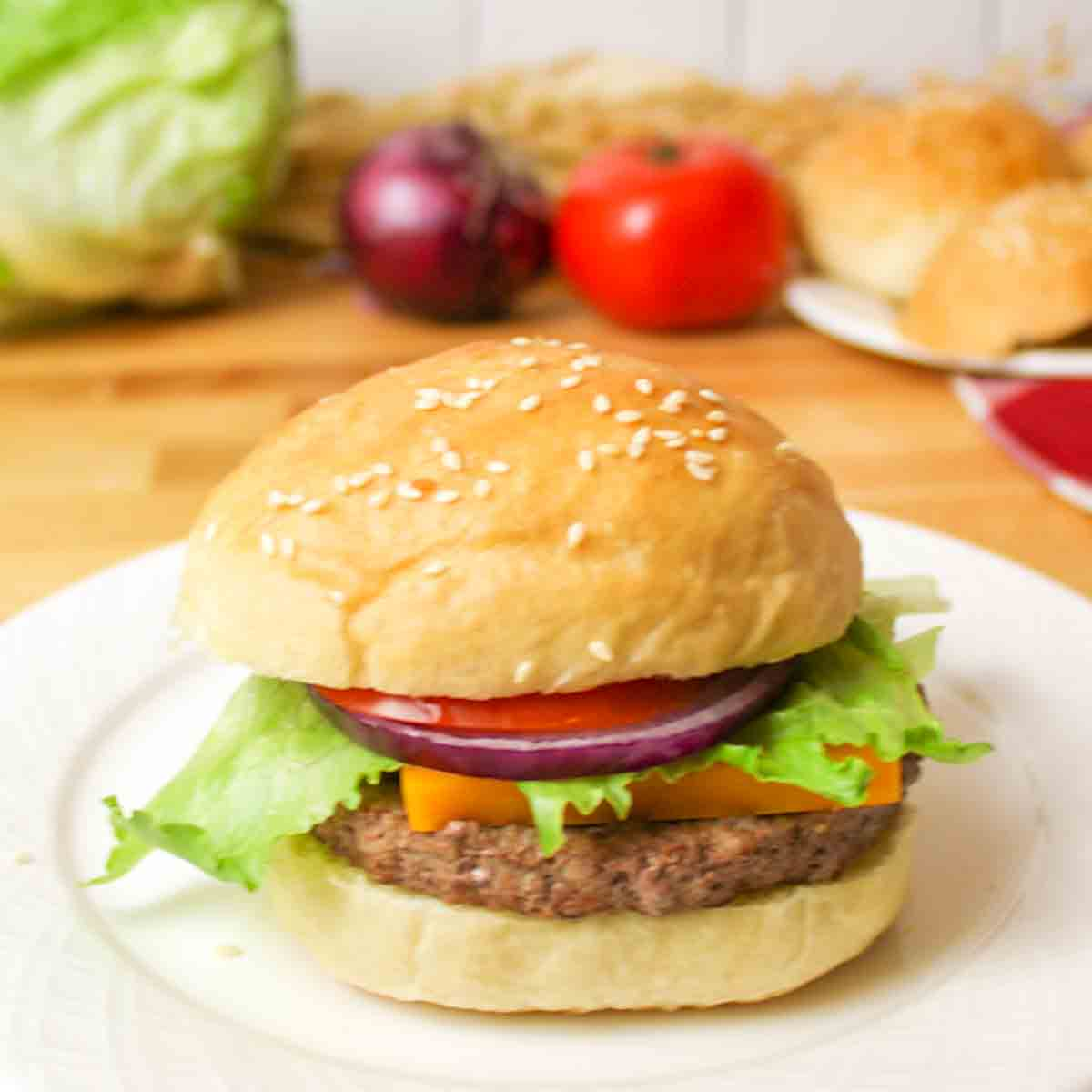 an upclose view of a fully assembled burger with homemade buns