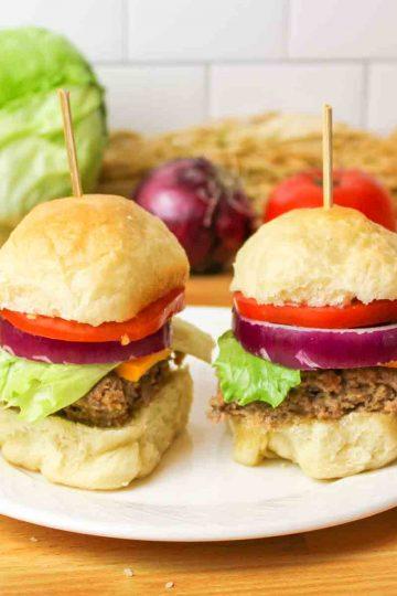 two vegan bun slider burgers on a white plate