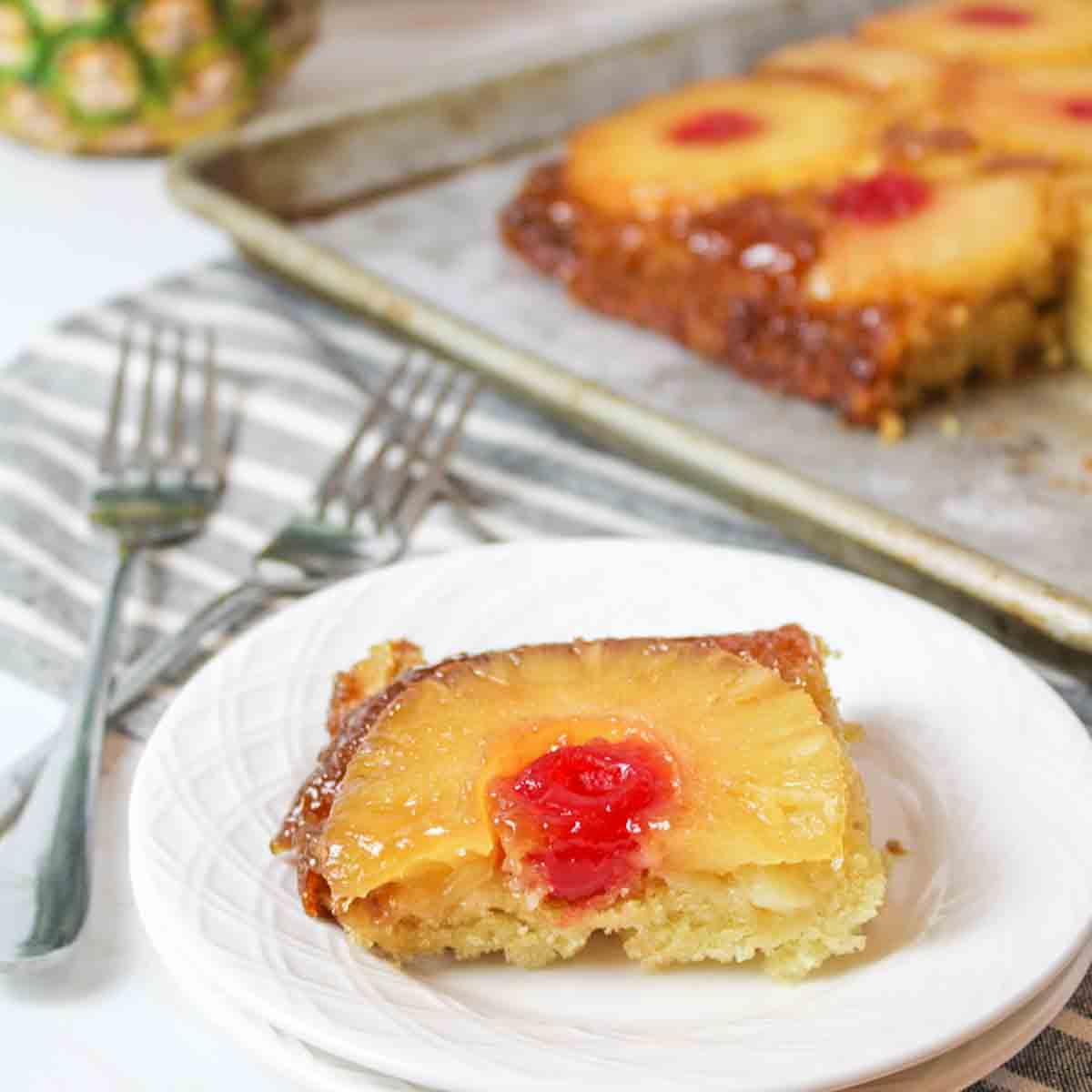 a close up of a slice of pineapple upside down cake with cherry on a white plate with forks and more cake in background