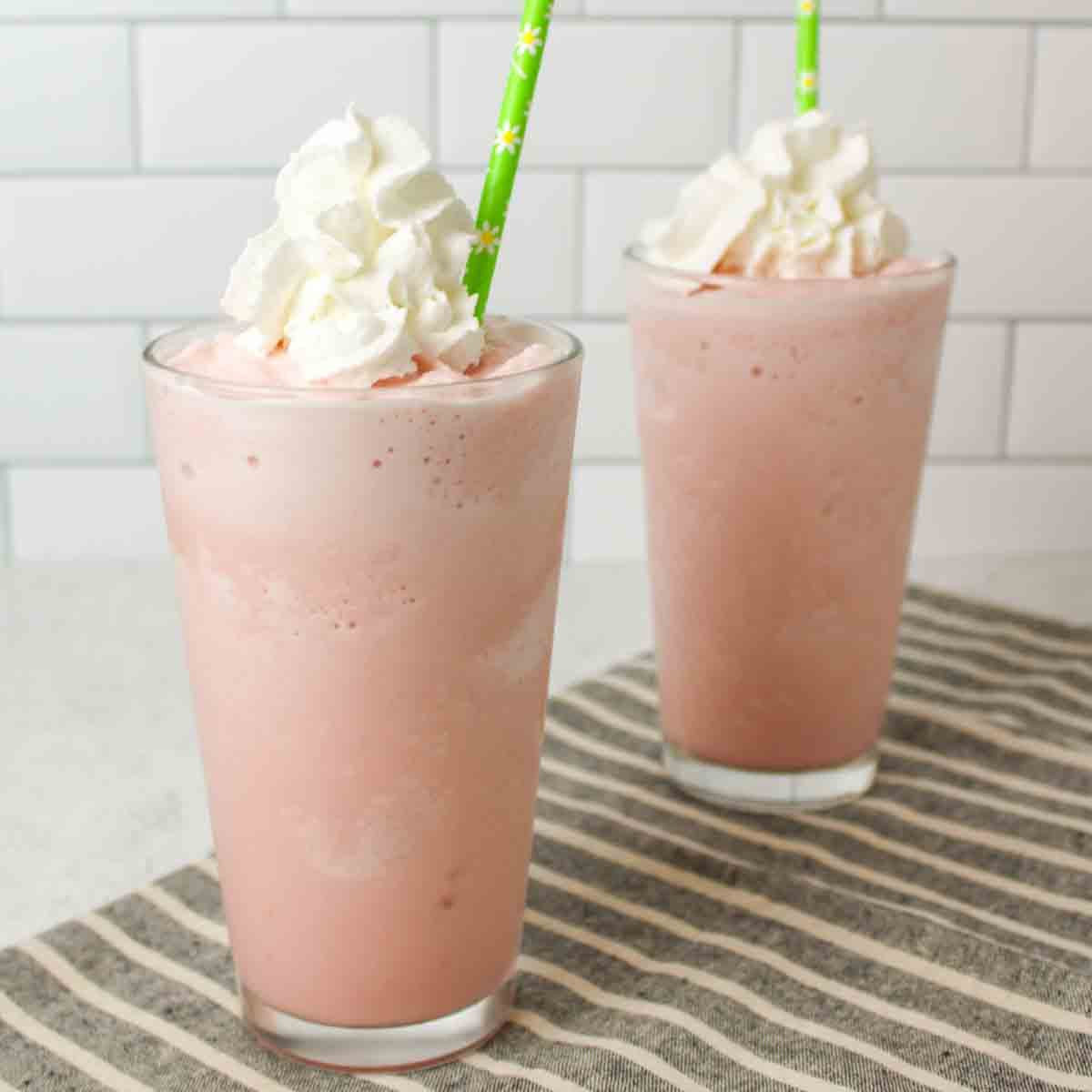 two glasses of light pink milkshakes with whipped cream and green straws
