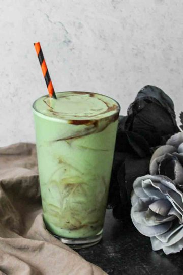 a green zombie milkshake in a glass next to flowers and a towel