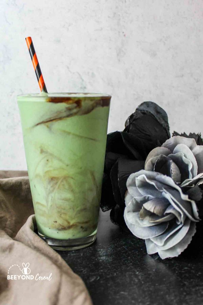 a side view of a zombie milkshake in a clear glass next to flowers