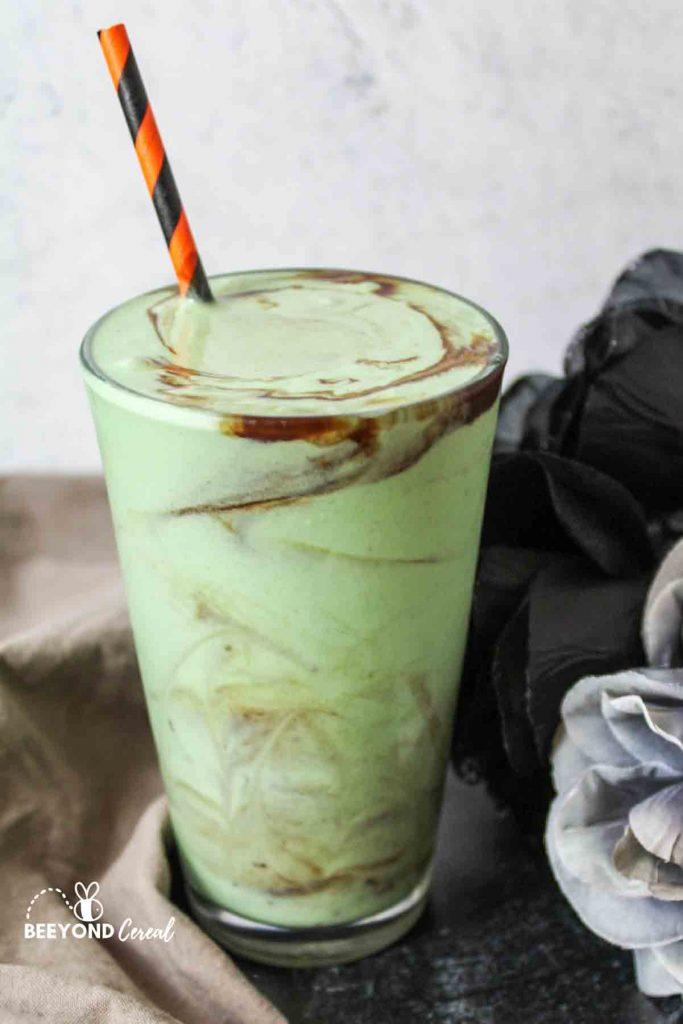 a green zombie milkshake with orange and black striped straw