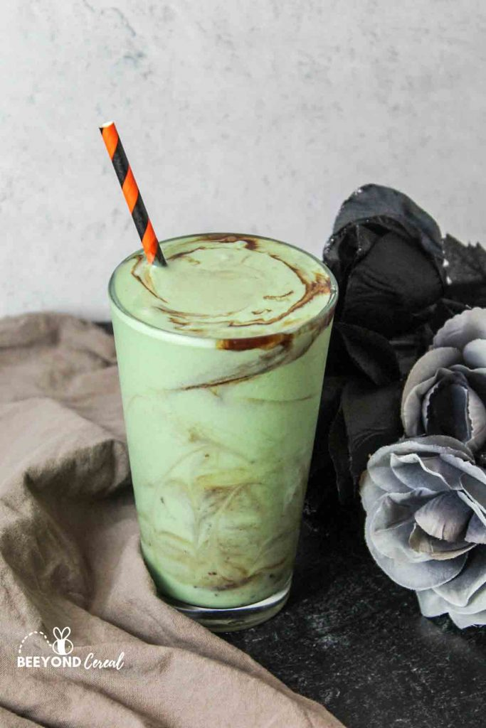 a chocolate swirled zombie shake in a cup next to flowers and a towel for props
