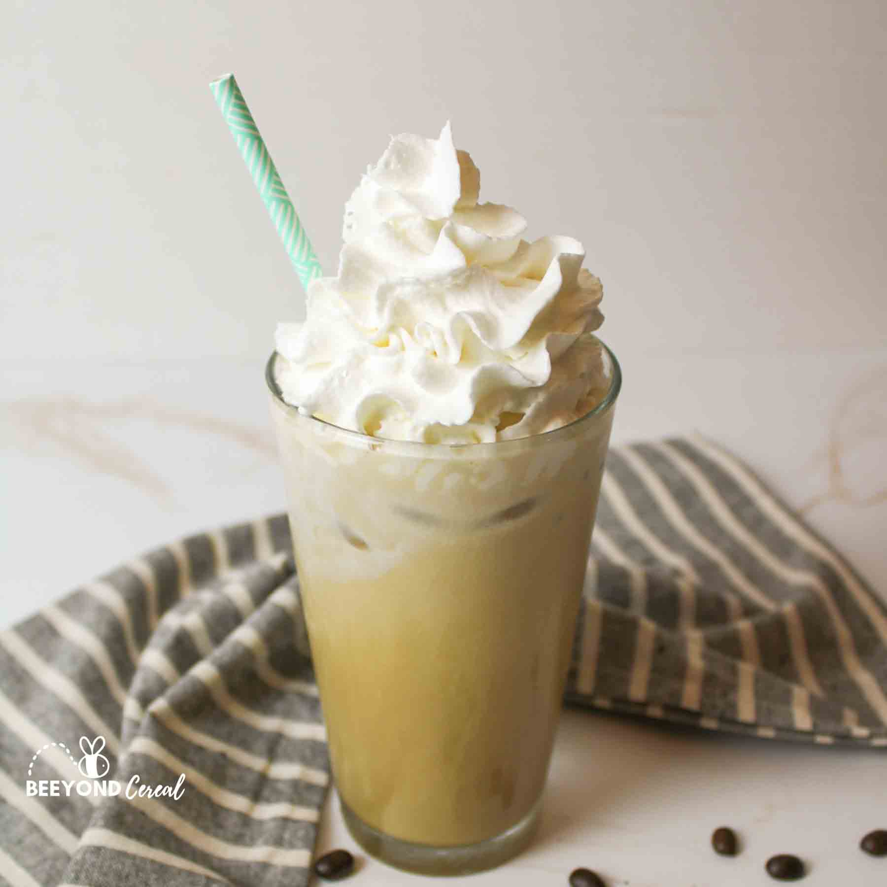 a glass of iced white chocolate mocha with whipped cream and a straw