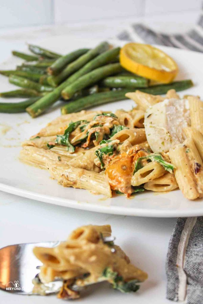a side angled view of a plate of pasta and green bean sides with a fork holding a bite of pasta in front out of focua