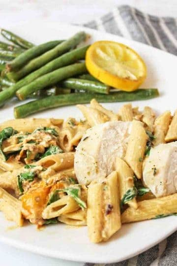 an upclose view of roasted garlic and tomato pasta with chicken and a pile of green beans and lemon slice in back