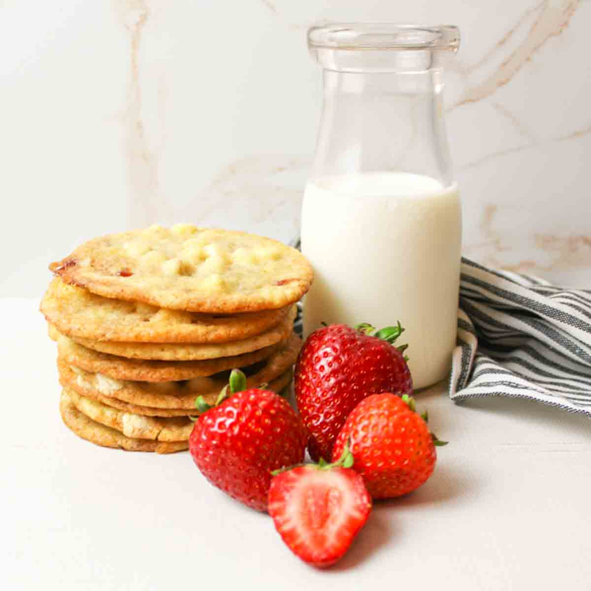 a close up of a stack of strawberries and cream cookies with fresh strawberries and a bottle of milk to the side