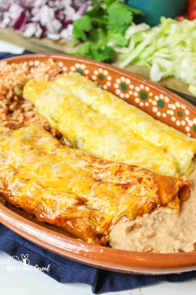 beef red suace and green chicken taqitos enchiladas on a plate with side dishes