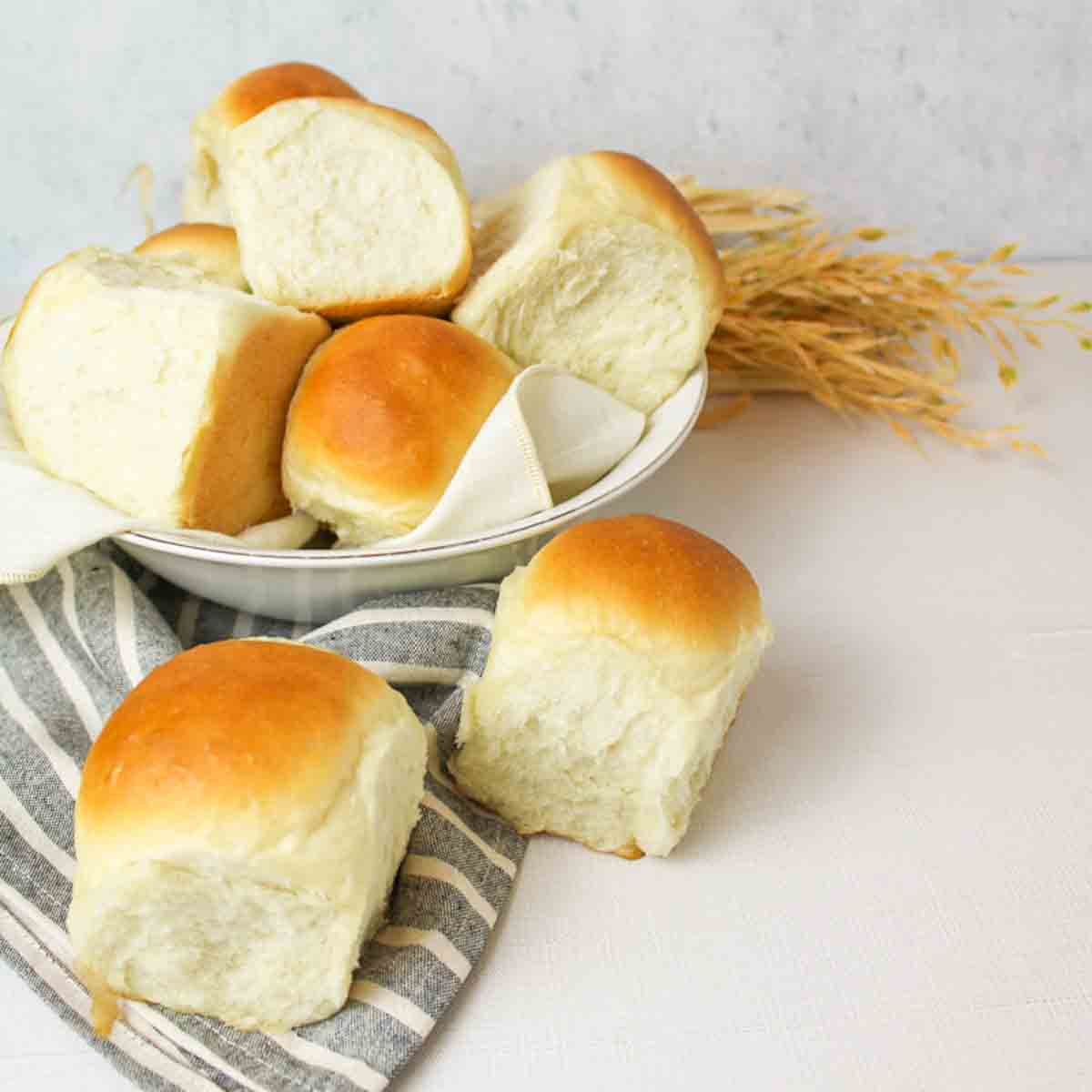 a close up of a bowl filled with vegan dinner rolls with a towel to the side and wheat in the background