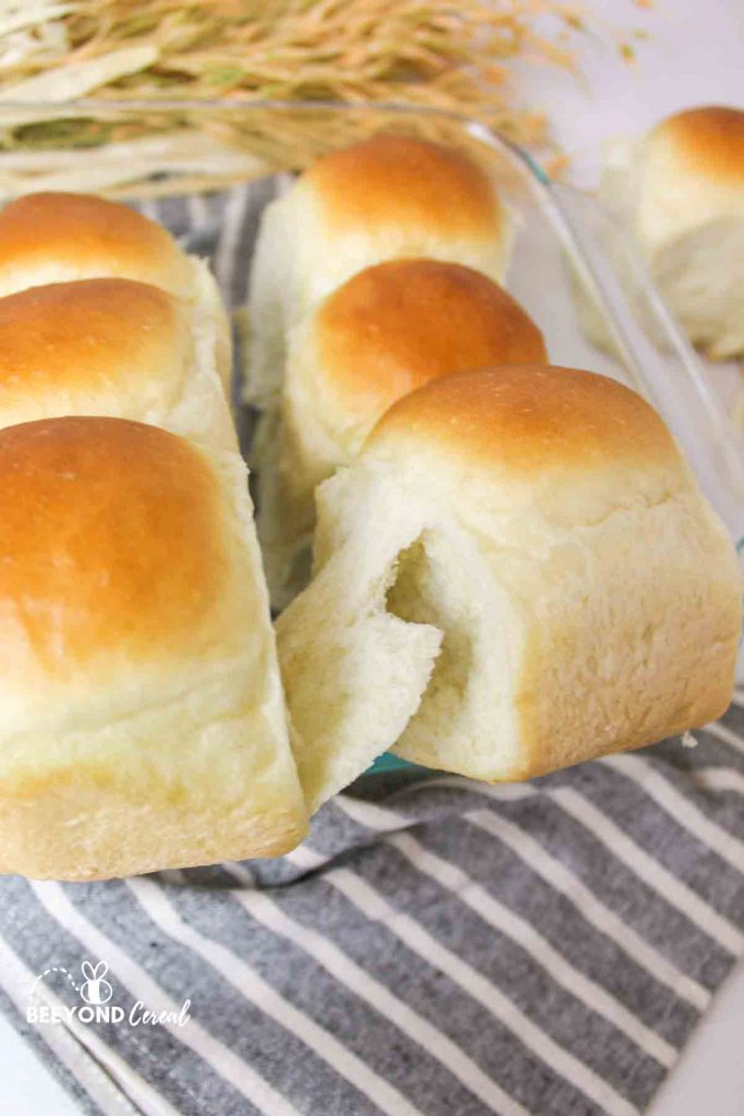 a baking dish full of bread rolls with a golden colored top and one roll being pulled away to reveal a flakey layer