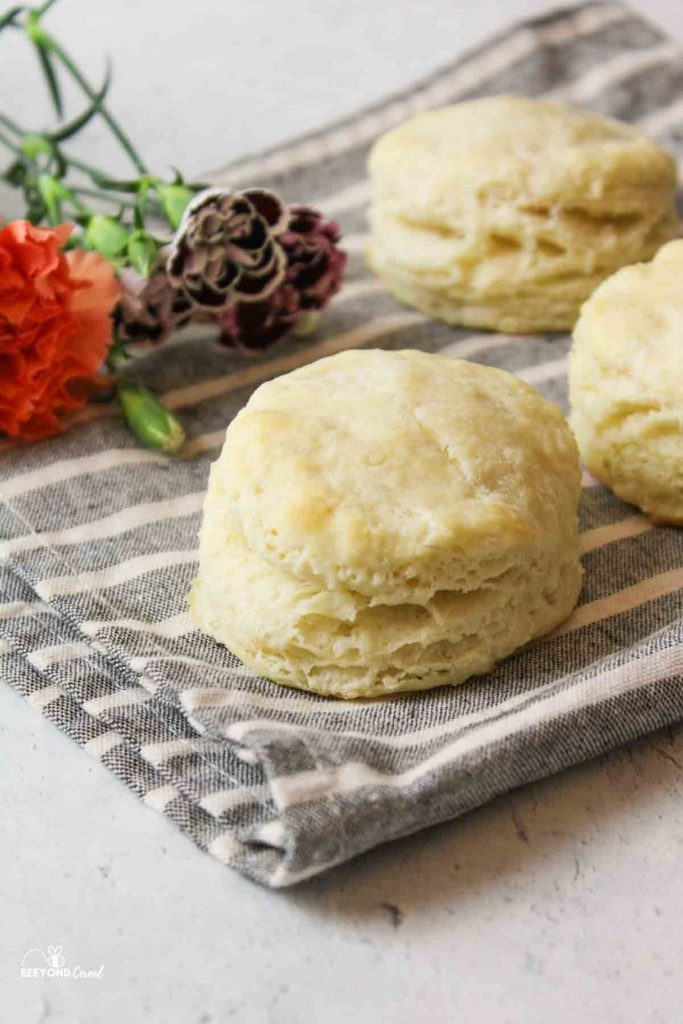 three biscuits on a striped towel with fresh flowers to the side