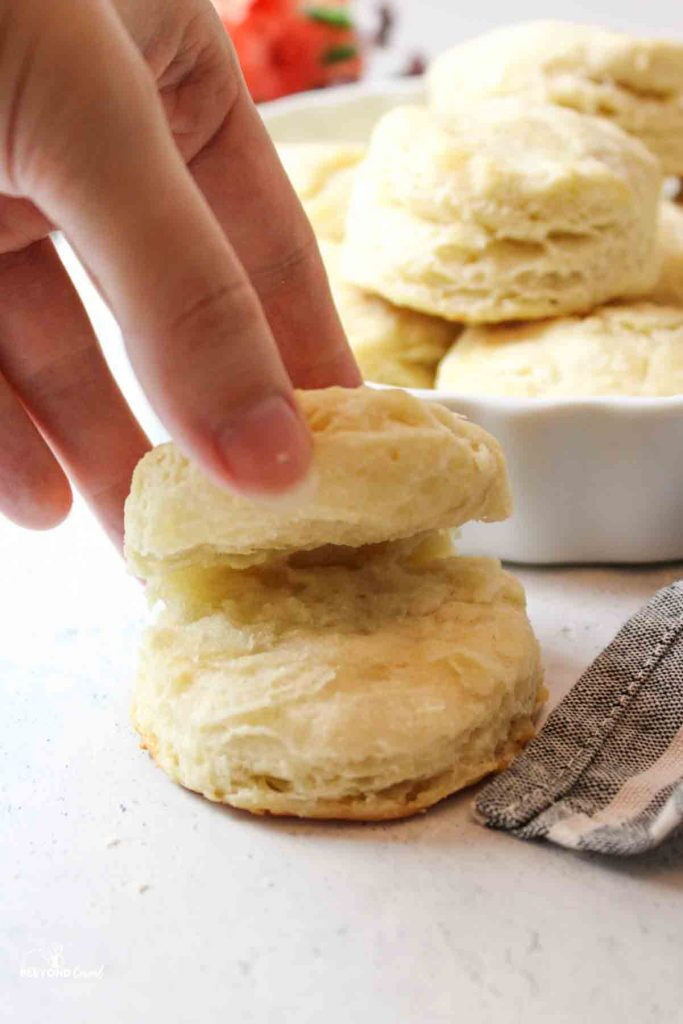 a hand holding a split biscuit to show the fluffy layers inside