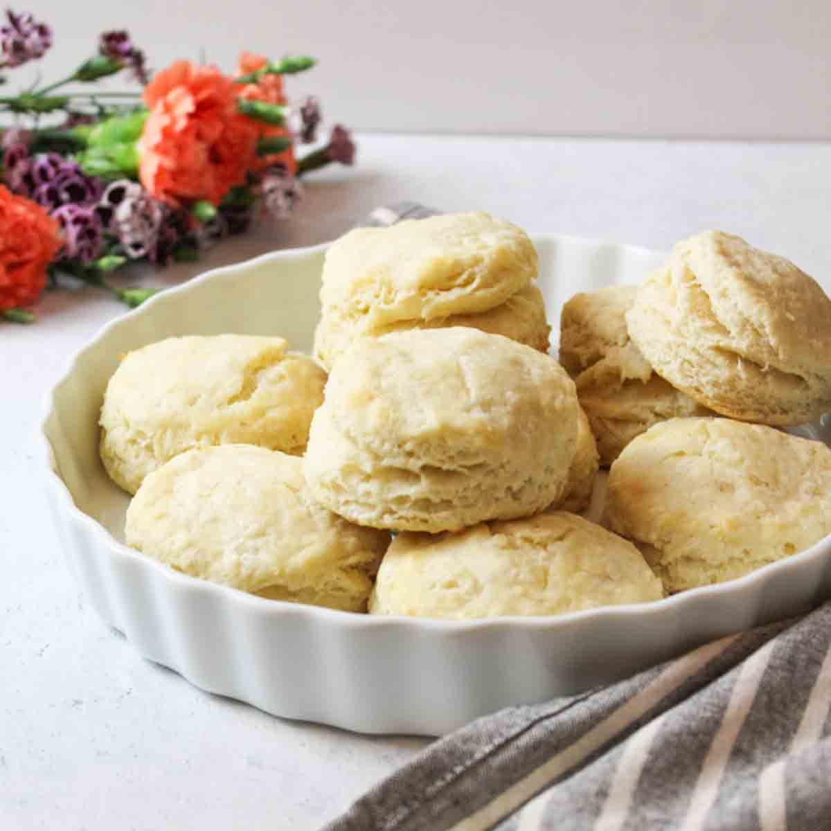 an uplcose view of a dish full of baking powder biscuit with fresh flowers in background