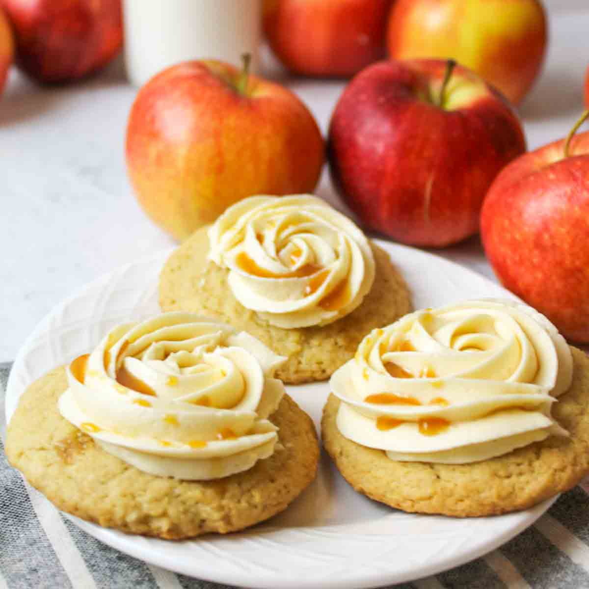three caramel buttercream topped apple cider cookies next to fresh red apples on a white plate
