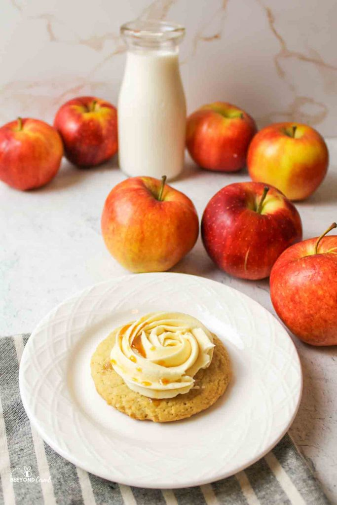 a caramel apple cider cookie on a white plate with fresh apples and a bottle of milk behind it