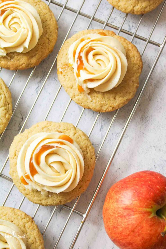 aerial view of caramel buttercream topped cookies on a wire rack with a red apple to the side