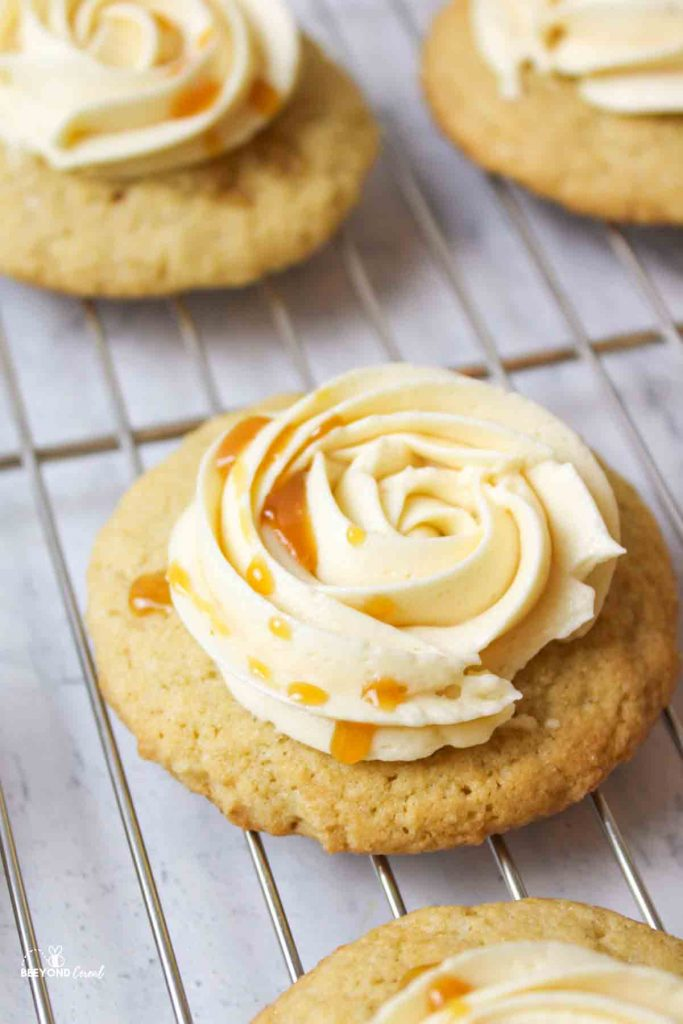 apple cider cookies on a wire rack topped with a rosette of frosting and drizzled in caramel
