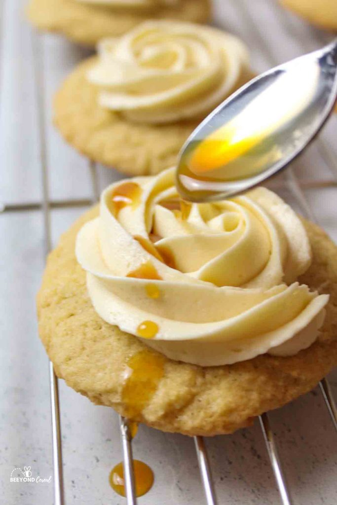 a sall spoon drizzling caramel syrup onto a frosting topped cookie