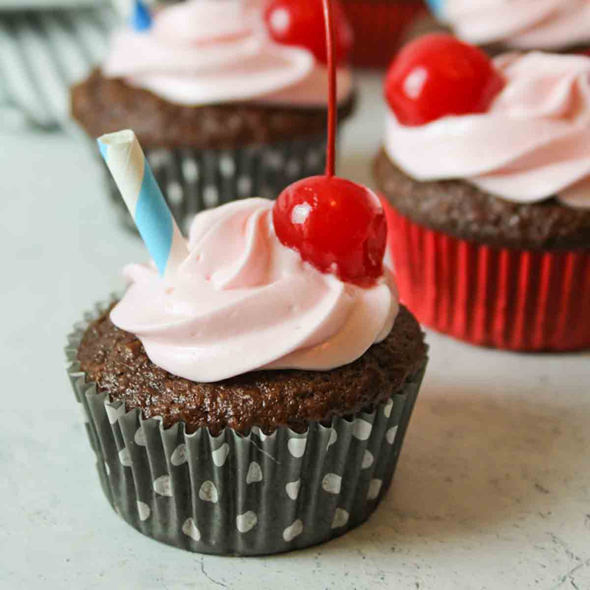a close up of a cherry coke cupcake with cherry and straw for garnish