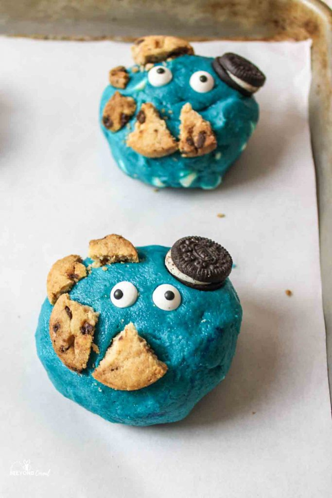 large blue cookie dough balls topped with candy eyes and broken cookie pieces