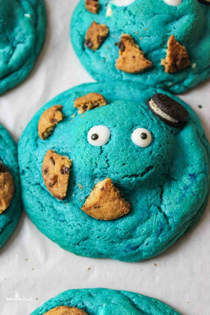 a close up of a blue cookie with candy eyes an broken smaller cookies on it