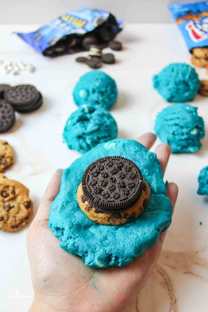 a hand holding a large blue dough topped with a chips ahoy cookie and oreo