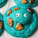 an upclose view of a blue cookie with eyes and cookie pieces on it