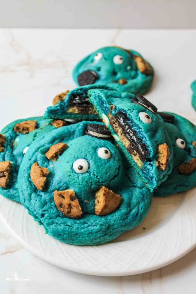 a plate full of blue cookies with eyes and other cookie pieces