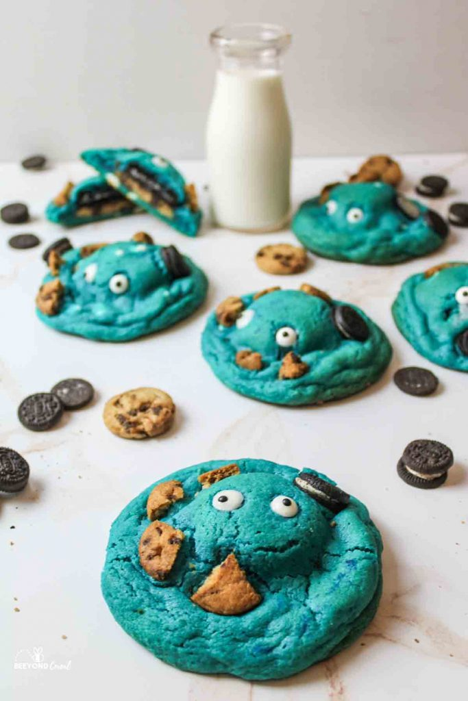 several arranged blue cookies with scattered mini cookies and a glass of milk in the background