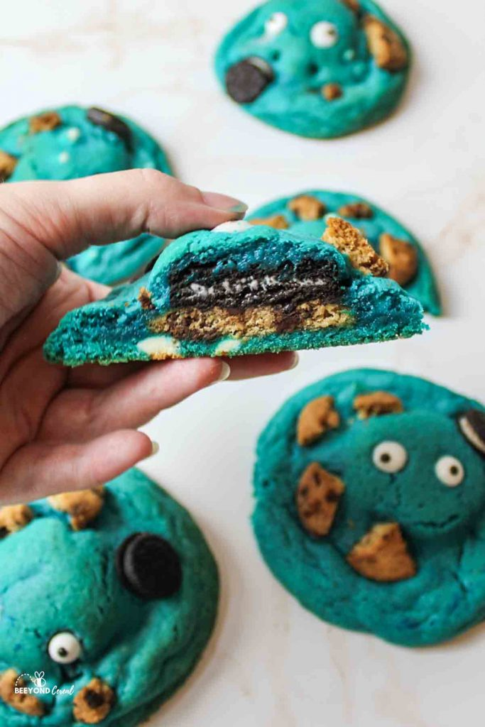 a hand holding up half of a cookie monster cookie above other scattered cookies