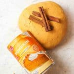 a ball of pumpkin playdough with two cinnamon sticks on top and a can of pumpkin puree to the side