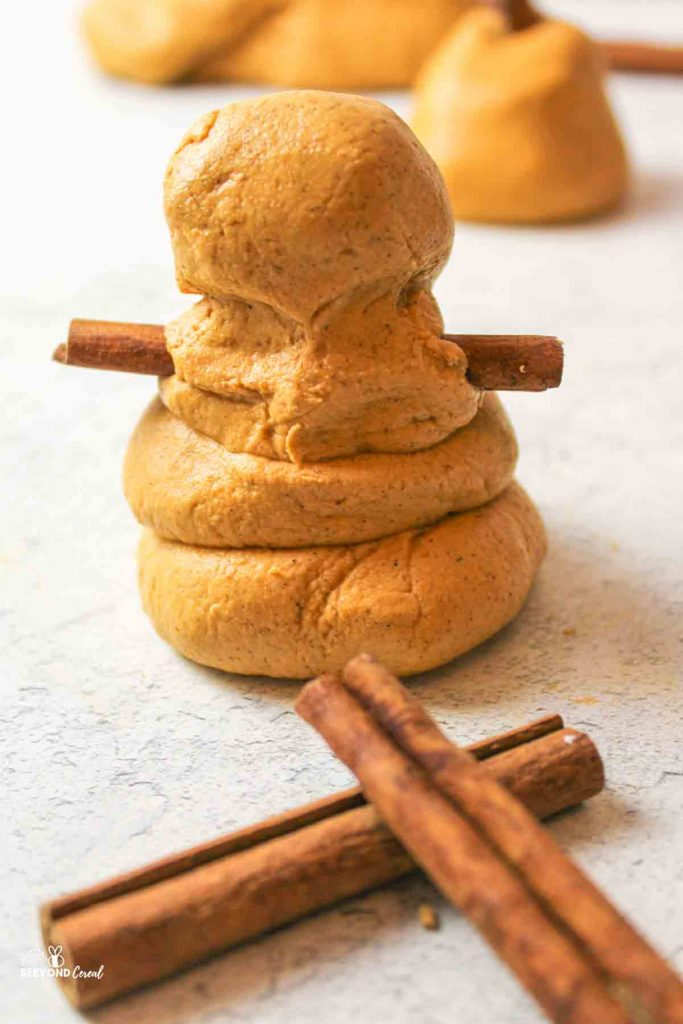 a small snowman shape made from pumpkin playdough with cinnamon stick arms and cinnamon sticks in front