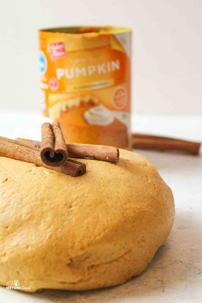 a large ball of pumpkin playdough with cinnamon sticks on top and a can of pumpkin puree in the background