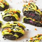 upclose view of halloween cookies with one broken open to reveal purple filling