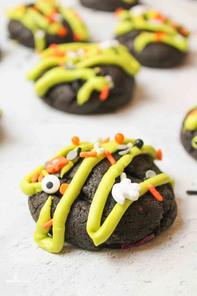a halloween cookie with green drizzle and halloween sprinkles