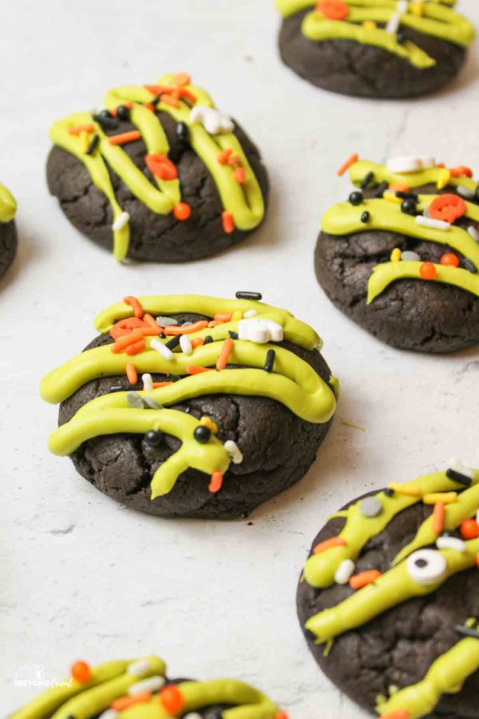 several halloween cookies with green drizzle and sprinkles on top