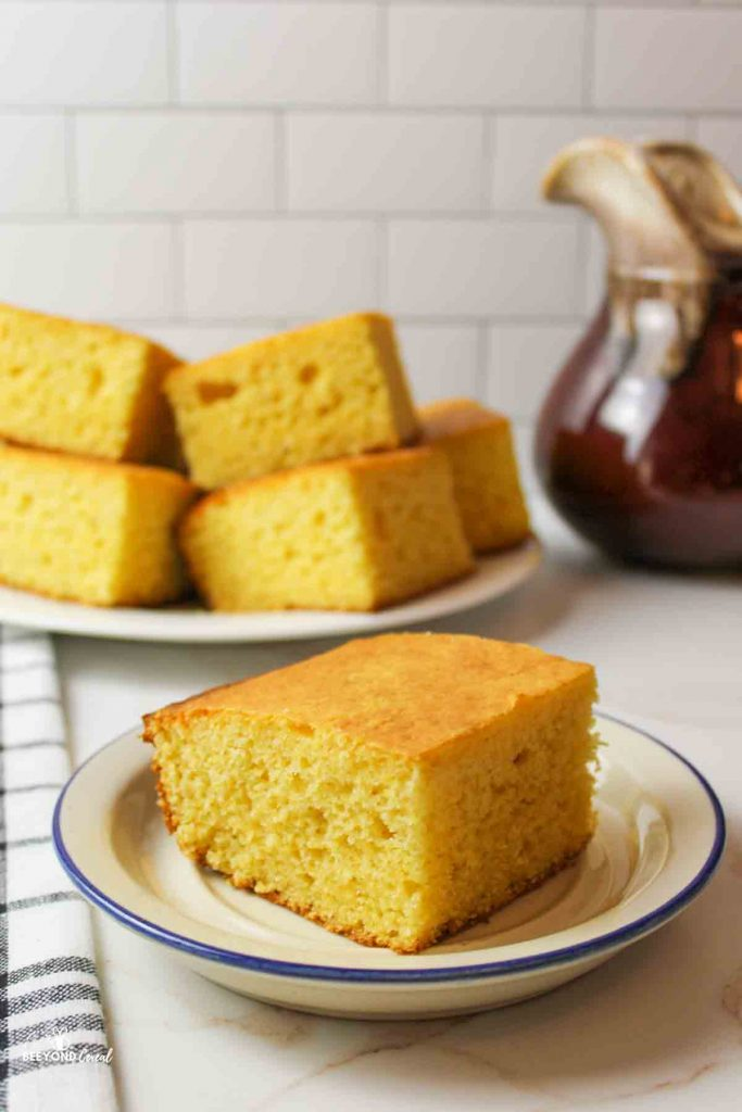 a slice of cornbread on a plate with more in the background