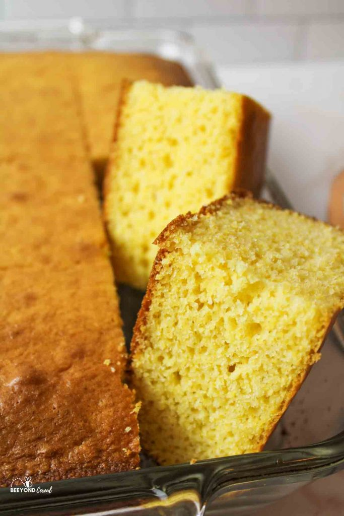 close up view of sliced cornbread turned sideways in a baking dish